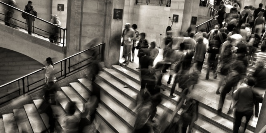 A crowd of busy commuters, their images blurred by movement
