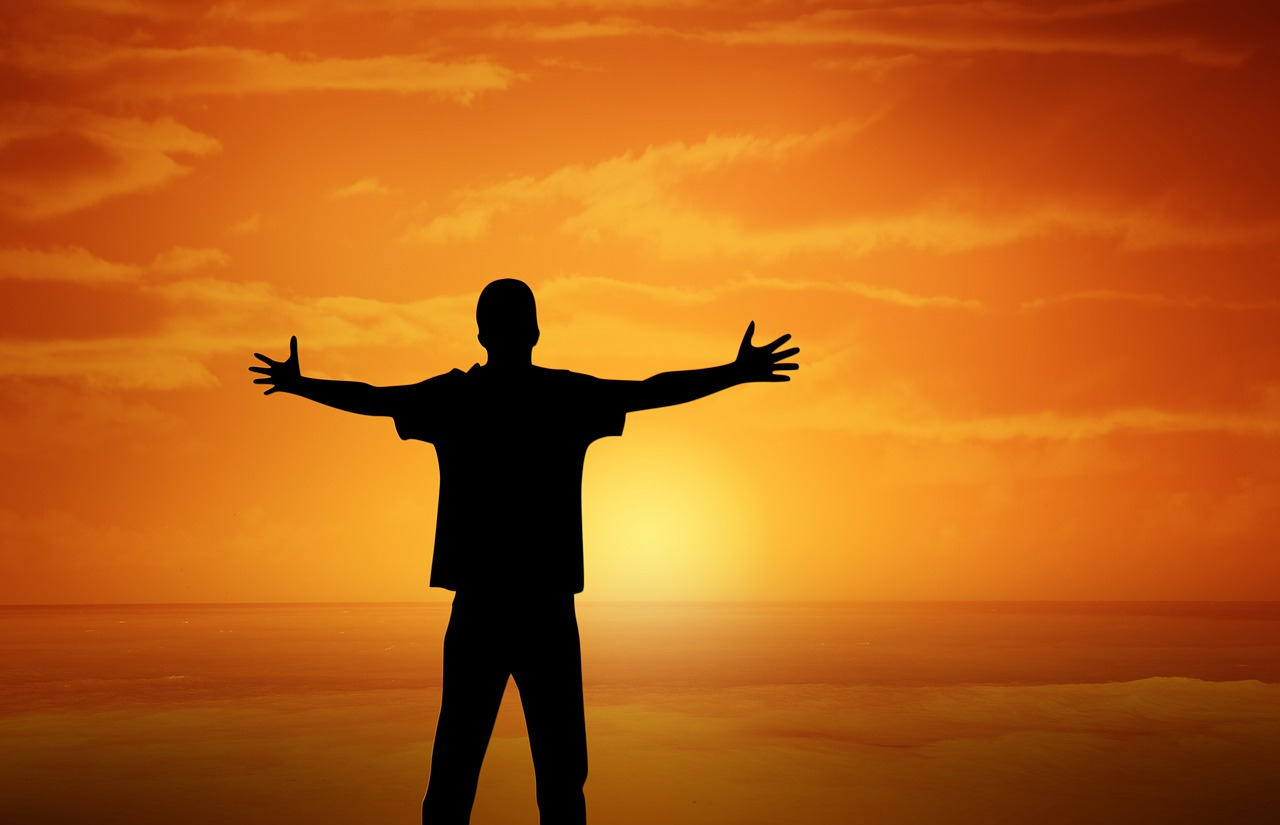 A man, arms outstretched in joy, silhouetted before a sunset