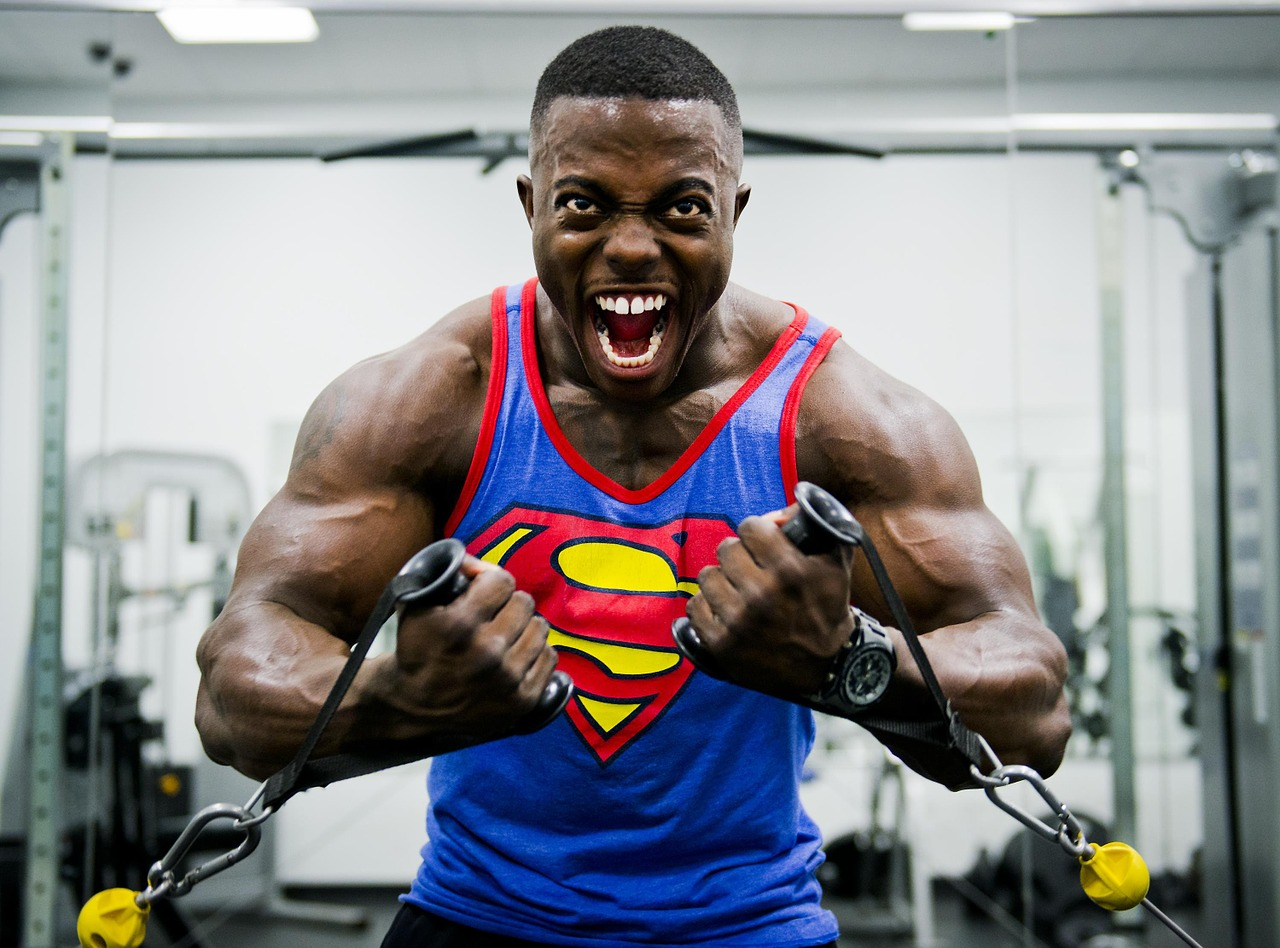 A bodybuilder, wearing a Superman tank top, using a set of cables in a gym