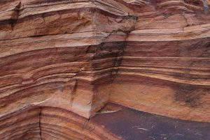 A cross-section view of a red sandstone rock formation, showing the numerous layers of rock