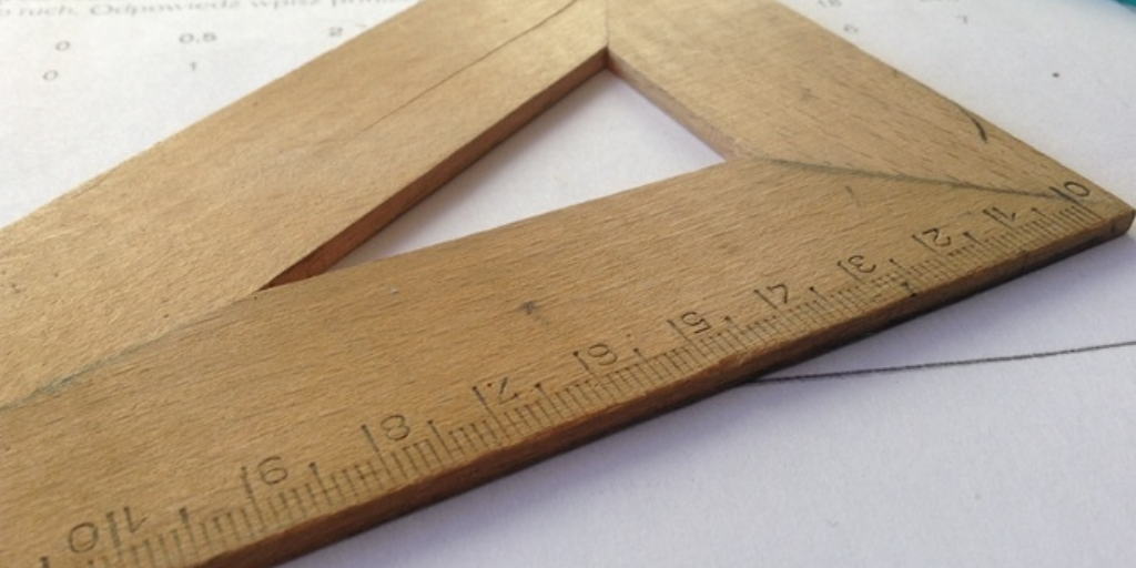 A wooden measuring rule, lying on a piece of paper