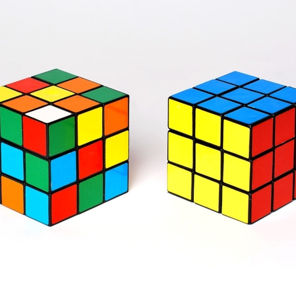 Two Rubik's Cubes, one unsolved and one solved, representing a changed mindset