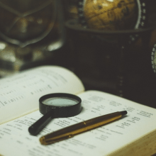 A book, magnifying glass and pen with a globe in the background - tools for language learning