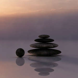 A pile of rocks, perfectly balanced and with a reflection - representing meditation