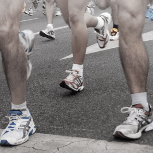 The legs of runners as they cross a finish line