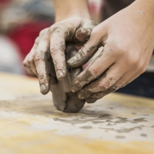 A person moulding a lump of clay with their hands, making art
